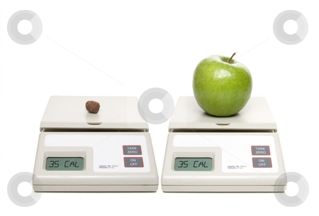 Healthy Choice stock photo, A scale with chocolate candy and one with an apple. by Robert Byron