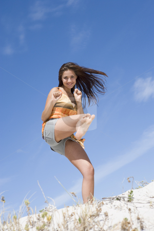 Young woman exercising on beach stock photo, Young woman kick boxing on beach by Monkey Business Images