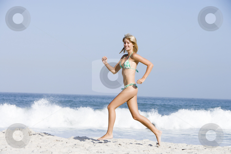 Young woman on beach holiday stock photo, Young woman on beach holiday wearing bikini by Monkey Business Images