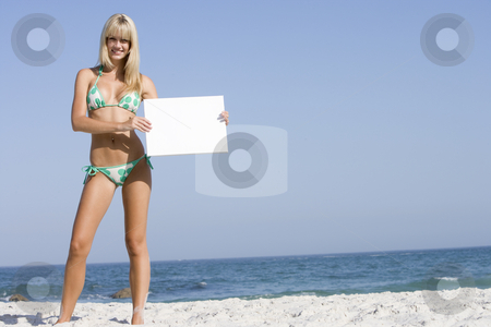 Woman on beach holding blank card stock photo, Woman on beach holding blank card wearing bikini by Monkey Business Images