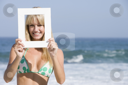 Woman looking through empty frame stock photo, Woman looking through empty frame on beach by Monkey Business Images