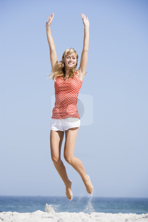 Young woman jumping on beach stock photo,  by Monkey Business Images