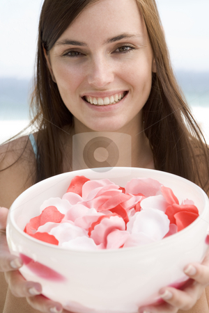 Woman holding bowl of petals stock photo,  by Monkey Business Images