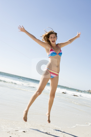 Woman leaping on beach stock photo, Woman wearing bikini leaping on beach by Monkey Business Images