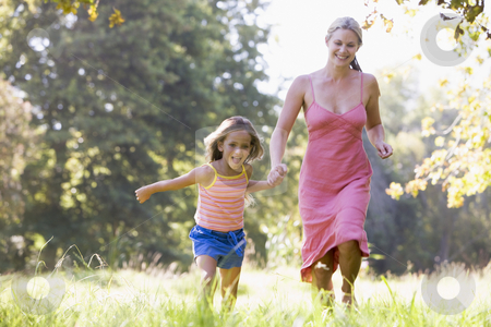 Woman and young girl running outdoors holding hands and smiling stock photo,  by Monkey Business Images
