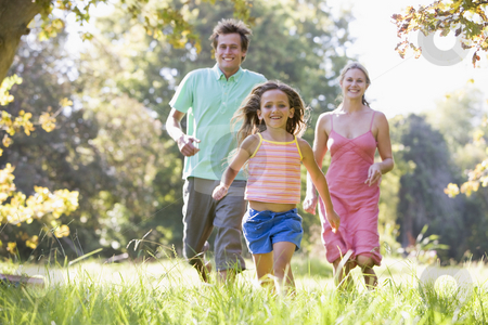 Family running outdoors smiling stock photo,  by Monkey Business Images