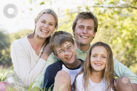 Family sitting outdoors smiling stock photo,  by Monkey Business Images