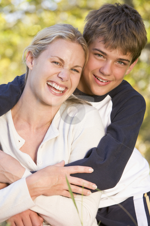 Woman and young boy embracing outdoors and smiling stock photo,  by Monkey Business Images