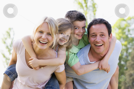 Couple giving two young children piggyback rides smiling stock photo,  by Monkey Business Images