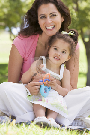 Woman and young girl sitting outdoors with toy smiling stock photo,  by Monkey Business Images