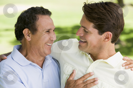 Two men standing outdoors bonding and smiling stock photo,  by Monkey Business Images