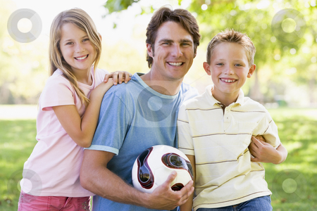 Man and two young children outdoors holding volleyball and smili stock photo,  by Monkey Business Images