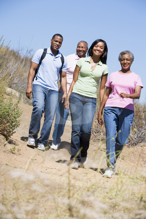 Two couples walking on path smiling stock photo,  by Monkey Business Images