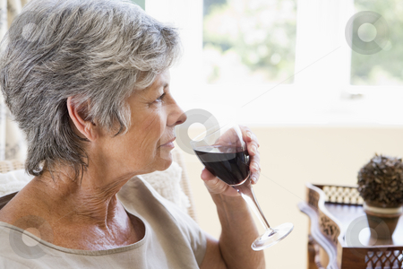 Woman in living room with glass of wine stock photo,  by Monkey Business Images