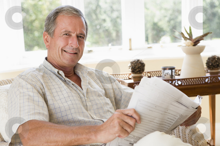 Man in living room reading newspaper smiling stock photo,  by Monkey Business Images