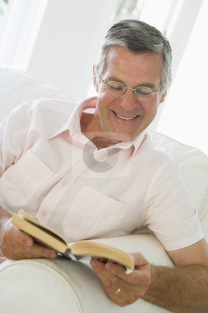Man in living room reading book smiling stock photo,  by Monkey Business Images