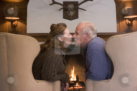 Couple sitting in living room by fireplace kissing stock photo,  by Monkey Business Images