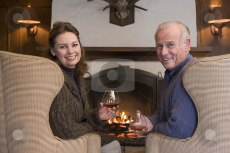 Couple sitting in living room by fireplace with drinks smiling stock photo,  by Monkey Business Images