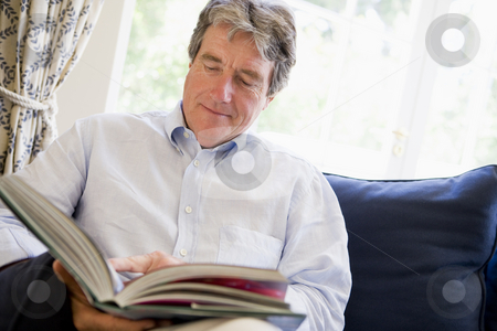 Man relaxing with book in living room stock photo,  by Monkey Business Images