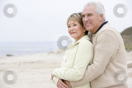 Couple at the beach embracing and smiling stock photo,  by Monkey Business Images