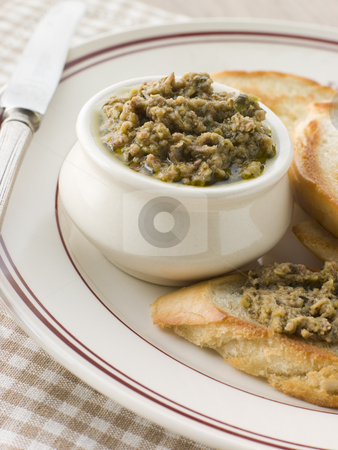 Green Olive Tapenade with toasted baguette stock photo,  by Monkey Business Images