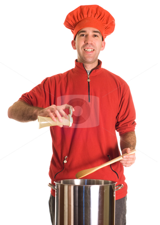 Spicy Soup stock photo, A young chef wearing red is adding some ground pepper to his pot of soup by Richard Nelson