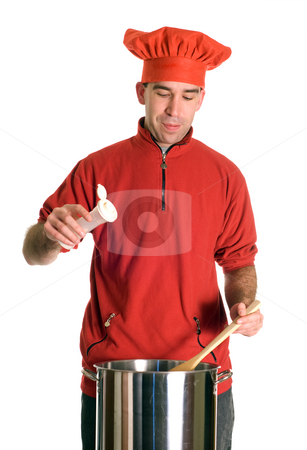 Salty Soup stock photo, A young chef adding some salt to his pot of soup, isolated against a white background by Richard Nelson