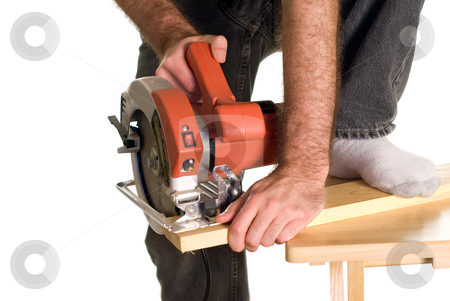 Dangerous Work stock photo, A man bracing a piece of wood with his foot in order to cut a piece of lumber with a skilsaw by Richard Nelson
