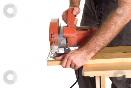 Cutting Lumber stock photo, A man using a skilsaw to cut a piece of wood, but has is finger in a dangerous position by Richard Nelson