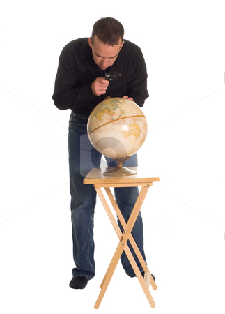 Looking At The Earth stock photo, Full body view of a man using a magnifying glass to examine a model of the earth by Richard Nelson