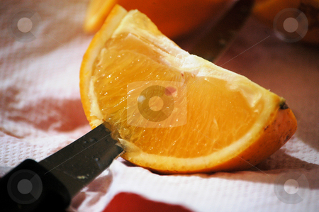 Cut the orange stock photo, Cutting an orange quarter so that it can be eaten by Tim Markley