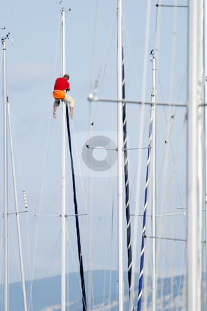 Man on a mast stock photo, Man working attached on the top af a sailboat mast by Massimiliano Leban