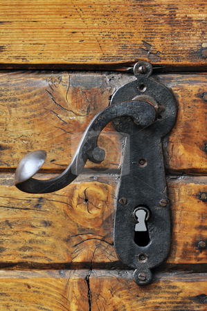 Door handle stock photo, Close-up of an old iron handle on a wooden front door by Massimiliano Leban