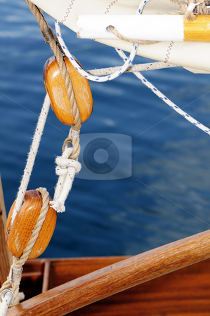 Old sailing pulleys stock photo, Close-up of wooden blocks on a old-fashioned sailboat with blue sea in background by Massimiliano Leban