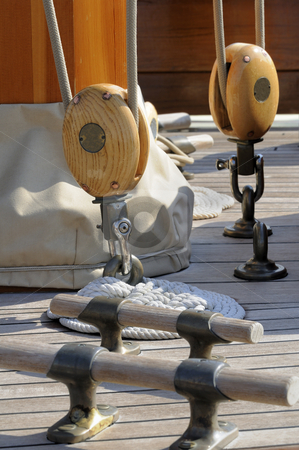 Sailboat tools stock photo, Detail of a deck on a wooden sailboat with bitts and blocks by Massimiliano Leban