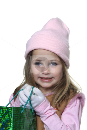 Little girl giving Christmas gift stock photo, Little girl with hat and gloves dressed for cold winter weather and holding a green christmas gift bag isolated on white by Anita Peppers