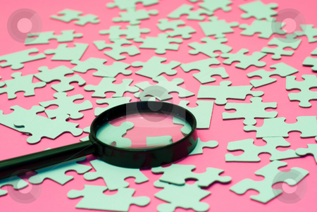 Magnifying Glass Puzzle stock photo, A mganifying glass resting on some puzzle pieces, shot on a pink background by Richard Nelson