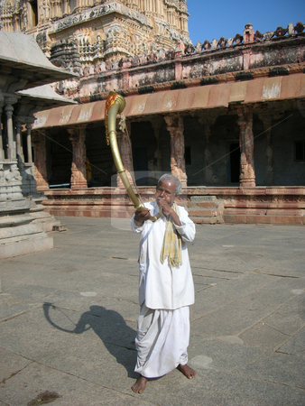 Discover India stock photo, A man plays a special type of trumpet / instrument inside a hindu temple premises in Hampi, an UNESCO World Heritage Site. by S Viswakumar