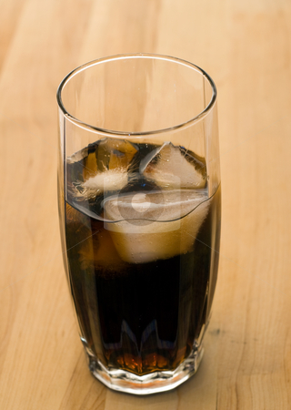 Cold Cola stock photo, A tall glass of cold cola, shot on a wooden table by Richard Nelson