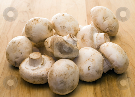 Fresh Mushrooms stock photo, A pile of fresh button mushrooms, shot on a wooden table by Richard Nelson