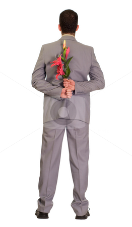 Romance stock photo, Full body view of a man wearing a suit holding some fake flowers behind his back by Richard Nelson
