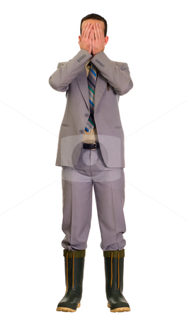 Embarassed Businessman stock photo, Full body view of an embarassed businessman wearing a grey suit and covering his face because he is wearing rubber boots by Richard Nelson