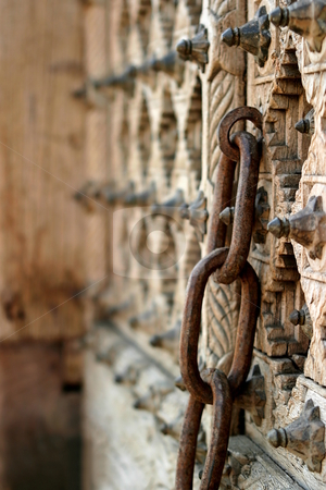 Chain stock photo, Rusty chain on an old wooden door. by Henrik Lehnerer