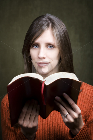 Woman with Bible stock photo, Pretty woman in orange sweater with Bible by Scott Griessel