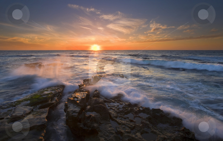 Reaching for the Sun stock photo, Waves crash over a rock shelf near the coast of La Jolla, California as the sun sets. by Mike Dawson
