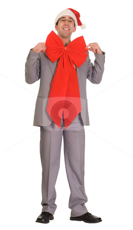 Christmas Businessman stock photo, Full body view of a businessman wearing a santa cap and a large red bow by Richard Nelson