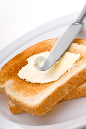 Spreading peanut butter on toast stock photo, A knife spreading butter on toast on a white plate by Vince Clements