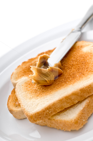 Spreading peanut butter on toast stock photo, Spreading peanut butter on toast by Vince Clements