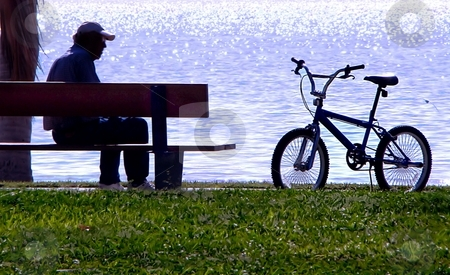 Remembering youth stock photo, Old man sitting on park beach whilst at beach looking at a bike by Kaye Terrelonge