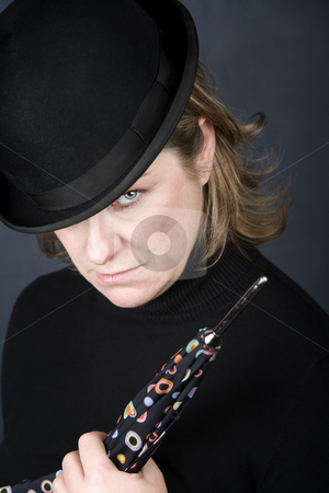 Woman in a bowler hat with umbrella stock photo, Woman in bowler hat with spotted umbrella by Scott Griessel